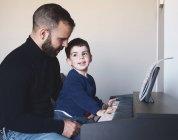 Vista lateral do homem barbudo adulto ensinando o menino a tocar piano digital em casa — Fotografia de Stock