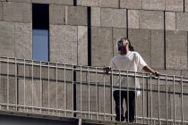 Jeune homme afro-américain appuyé sur la rampe du pont sur la rue de la ville par une journée ensoleillée — Photo de stock