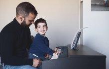 Взгляд сбоку на взрослого бородатого мужчину, который учит маленького мальчика играть дома на цифровом пианино — стоковое фото
