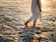Retrato de cultura encantadora menina em vestido branco andando na água na praia ao pôr do sol — Fotografia de Stock