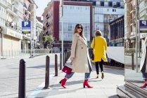 Jeune femme à la mode heureuse dans le trench-coat et les lunettes de soleil marchant dans la ville — Photo de stock
