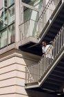 Молодой афроамериканец опирается на перила моста в городе — стоковое фото