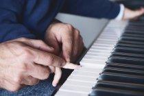 Перекручений образ батька, який допомагає малому хлопчику штовхати ключі під час уроку гри на фортепіано вдома. — стокове фото
