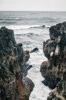 Mare grigio che scorre tra le rocce nelle giornate nuvolose — Foto stock