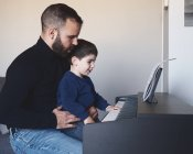 Side view of adult bearded man teaching little boy to play digital piano at home — Stock Photo