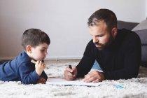 Homem barbudo adulto sorrindo e olhando focado menino desenho com caneta marcador enquanto deitado no chão em casa juntos — Fotografia de Stock