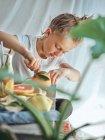 Niño en camiseta blanca corte naranja con hojas verdes para el jugo en la cocina en el día de verano - foto de stock