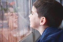 Vista lateral de niño divertido respirando en vidrio de ventana mojado mientras pasa tiempo en casa en el día lluvioso - foto de stock