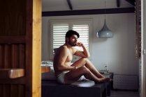 Joven hombre sexy penoso y exitoso con estilo de pelo en los cuadros grises tumbado en la cama en casa y mirando hacia atrás. - foto de stock