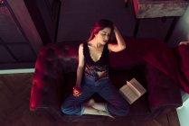 Молода сексуальна жінка сидить на дивані з яблуком і книгою — стокове фото