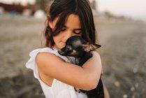 Portrait d'enfant charmante femme en robe blanche tenant petit chien sur la plage — Photo de stock