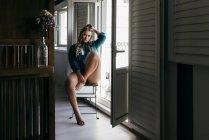 Joven mujer seductora posando en silla cerca de balcón - foto de stock