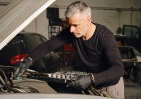 Adult male mechanic in gloves using tools to fix vehicle in garage — Stock Photo
