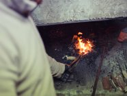 Blacksmith hand heating metal in ancient oven on coals in traditional smithy — Stock Photo
