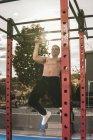 Jeune homme torse nu effectuant pull ups sur le bar pendant l'entraînement sur la rue de la ville le jour ensoleillé — Photo de stock