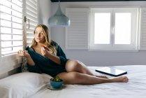 Молодая женщина лежит на кровати с клубничной чашей — стоковое фото