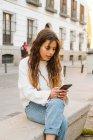 Jovem do sexo feminino em roupa casual sentado e navegando smartphone na rua da cidade — Fotografia de Stock
