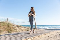 Barefoot girl in casual outfit and glasses reading book while walking on lumber path on beach near waving sea — Stock Photo
