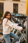 Веселая молодая женщина в повседневной одежде сидит на арендованном велосипеде на станции обмена и смотрит в камеру на городской улице — стоковое фото
