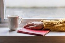 Main de personne en pull chaud confortable jaune avec livre et tasse de thé sur le rebord de la fenêtre . — Photo de stock