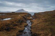 Ruscello d'acqua e strada asfaltata sinuosa che attraversa terreni collinari durante il giorno nuvoloso sulle Isole Faroe . — Foto stock