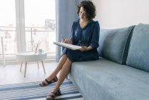 Элегантная женщина, сидящая дома на диване и рисующая на блокноте — стоковое фото
