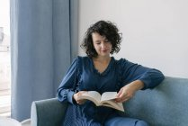 Happy young brunette woman in blue dress reading book sitting on couch at home — Stock Photo