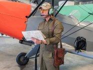 Piloto segurando mapa perto de pequeno avião no hangar — Fotografia de Stock