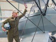 Piloto confiante em pé perto de avião retro no hangar e segurando capacete — Fotografia de Stock