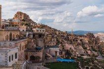 Casas de piedra de mala calidad de la ciudad vieja situada en la montaña áspera contra el cielo nublado de Capadocia, Turquía — Stock Photo