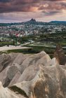 Peak of rough rock formation in amazing countryside against overcast sky and distant city in Cappadocia, Turkey — Stock Photo