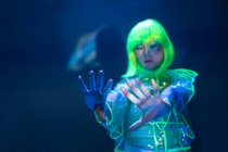 Young asian woman in yellow wig and transparent plastic wear posing in fluorescent light with raised hands — Stock Photo