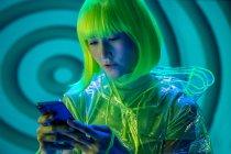 Junge Asiatin in futuristischer Kleidung und grüner Perücke mit Smartphone in Leuchtstoffröhren — Stockfoto