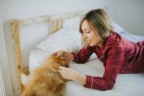 Mulher atrativa de sorriso feliz nova nos pijamas que encontram-se na cama com o cão macio pequeno — Fotografia de Stock