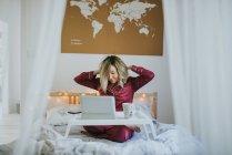 Молода симпатична жінка в піжамі розтягування в ліжку, сидячи в настільний лоток з таблетці і ранкової чашки кави — стокове фото