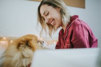 Молодая счастливая улыбающаяся привлекательная женщина в пижаме сидит в постели с маленькой пушистой собачкой — стоковое фото