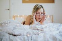 Молодая женщина в очках и нижнем белье лежит в постели утром — стоковое фото