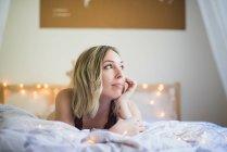 Mulher nova no roupa interior que encontra-se na cama com luzes — Fotografia de Stock