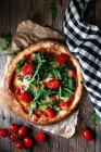Pizza deliciosa com tomates, rúcula e mozzarella no fundo de madeira rústico — Fotografia de Stock