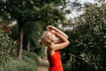 Side view of attractive blonde dressed in red sensually posing with closed eyes among green blooming trees — Stock Photo