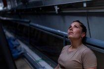 Привлекательная женщина-солдат смотрит вверх, сидя внутри современного военного транспорта — стоковое фото