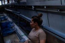 Серьёзная военная женщина в форме смотрит в сторону, сидя на полу армейского транспорта — стоковое фото