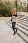 Jovem mulher em elegante boina vermelha olhando para longe enquanto caminhava para baixo na rua da cidade — Fotografia de Stock