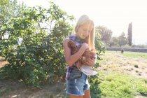 Chica adolescente y en camisa a cuadros y denim gallina de mascotas cortas mientras está de pie cerca de arbustos verdes en el día soleado en la granja - foto de stock