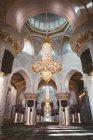 З нижче відкривається вид на мечеть в інтер'єрі з світяться золотою лампою і декоративні колони, Дубаї — стокове фото