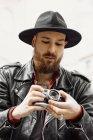 Молодий бородатий вродливий чоловік у чорному капелюсі і шкіряній куртці фотографується на вулиці — стокове фото