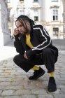 Junge ethnische Mann mit geflochtenen Haaren trägt schwarzen Sportanzug hockt und blickt in die Kamera auf städtischem Hintergrund — Stockfoto