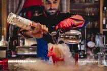 Бармен в форме и красных перчатках сконцентрировался на приготовлении коктейля и разливке напитков для курения коктейля — стоковое фото