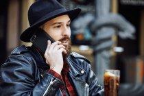 Молодий бородатий вродливий чоловік у чорному капелюсі і шкіряній куртці розмовляє по мобільному телефону на вулиці кафе — стокове фото