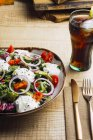 Vegetable salad with onion greens and cream sauce served on plate on wooden table — Photo de stock